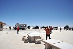 Turisti sugli appartamenti del sale di Uyuni, lago di sale inaridito in Altiplano Immagine Stock