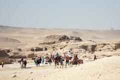 Turisti sul cammello in deserto vicino alle rovine a Giza fotografia stock