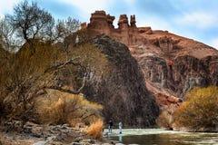 Turisti sul fiume della montagna contro lo sfondo delle rocce rosse Immagine Stock