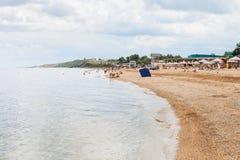 Turisti sulla sabbia e sul mare della spiaggia di Azov shelly Fotografie Stock Libere da Diritti