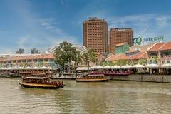 Turistic fartyg på den Singapore floden på Clarke Quay och flodstranden ar Arkivbild