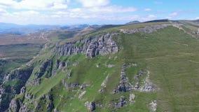 Turists que disfruta de la visión desde el pico de Caraiman, Rumania, vuelo aéreo almacen de metraje de vídeo