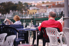 Turists reading newspaper on a esplanade on Algarve. Royalty Free Stock Images