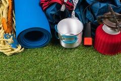 Turistuppsättning på en grön gräsmatta för en vandring i en expedition, med redskap för att laga mat i den öppna luften arkivfoton