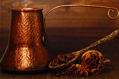Turk coffee pot and coffee beans with spices on the table. Traditional eastern style copper coffee pot with roasted coffee beans and spices on the table Royalty Free Stock Images