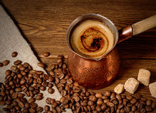 Turk with freshly brewed coffee on wooden background Royalty Free Stock Image