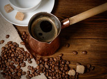 Turk with freshly brewed coffee on wooden background Royalty Free Stock Photos