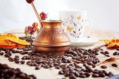Turk och korn av kaffe på en trätabell Arkivfoto