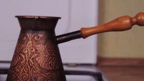 Turka καφέ στην πυρκαγιά Στο αέριο η σόμπα είναι χαραγμένος χαλκός Τούρκος Ζυθοποιός καφέ Άσπρη σόμπα αερίου με το κάψιμο της πυρ φιλμ μικρού μήκους
