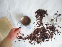 Turka for brewing coffee, a book, a cup with a spoon and coffee beans Stock Photography