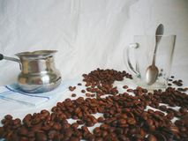 Turka for brewing coffee, a cup with a spoon and coffee beans Royalty Free Stock Images