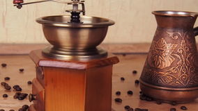 Turka with coffee and a coffee grinder. On the kitchen marble table there is a Turk and a coffee-mill. The coffee beans are scatte. Red. Slow motion stock video footage