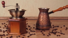 Turka with coffee and a coffee grinder. On the kitchen marble table there is a Turk and a coffee-mill. The coffee beans are scatte stock video footage
