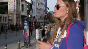 Turkey, Antalya, March 2016: a girl drinking coffee from a cup on the street. People walking on the street in the center of the city in the summer when the sun stock video footage