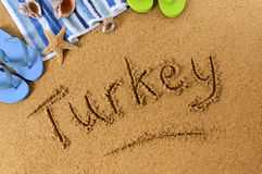 Turkey beach sand word writing. The word Turkey written on a sandy beach, with beach towel, starfish and flip flops Stock Photo