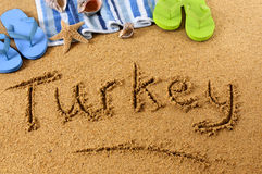 Turkey beach writing. The word Turkey written on a sandy beach, with beach towel, starfish and flip flops Royalty Free Stock Photography