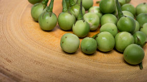 Turkey berry Solanum torvum on chopping wooden background. Turkey berry Solanum torvum on chopping wooden Stock Photo