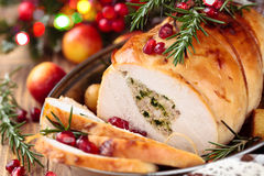 Turkey breast for holidays. Stuffed turkey breast with baked vegetables and spices against holiday lights background stock photography