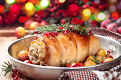 Turkey breast for holidays. Stuffed turkey breast with baked vegetables and spices against holiday lights background royalty free stock photography