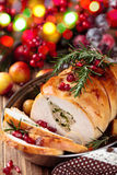 Turkey breast for holidays. Stuffed turkey breast with baked vegetables and spices against holiday lights background royalty free stock image