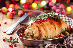 Turkey breast for holidays. Stuffed turkey breast with baked vegetables and spices against holiday lights background royalty free stock photos