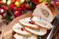 Turkey breast for holidays. Stuffed turkey breast with pomegranate and rosemary on cutting board stock photo