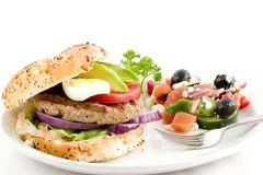 Turkey burger, greek salad. Turkey burger on an onion roll garnished with red onion, lettuce, egg avocado,and tomato slices served with a side of greek salad and royalty free stock images