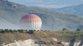 Hot air balloon striped with a basket of tourists flying high in the sky. Turkey, Cappadocia - 7 June 2019: Hot air balloon striped with a basket of tourists stock video footage