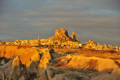 Turkey. Cappadocia. View on rock-castle of Uchisar. Town across a Guyercinlik valley at a sunrise royalty free stock image