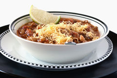Turkey Chili with Cheese and Lime. Bowl of turkey chili with cheese and lime slice and spoon Stock Image