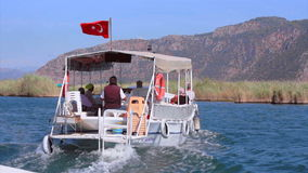 Turkey Dalian River. Touristic boat with the tourists have a journey across the river. people have a fan. cinema color effect stock video footage