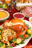 Turkey dinner. Holiday dinner with roast turkey, pumpkin pie, cranberry chutney, baked ham, dinner rolls and fruits royalty free stock photo