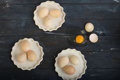 Turkey eggs in three white dishes and one broken egg on rough dyed wooden surface. Horizontal royalty free stock photography