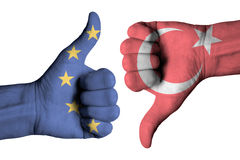 Turkey and Europe flag on human male thumb up and down hands. Turkey and Europe flag on human male thumb up and down  hands Royalty Free Stock Image