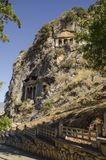 Turkey, Fethiye, Lycian tombs located on rocks, general view,. Rocks are lit by the sun, the slopes are covered with grass Royalty Free Stock Image