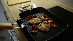Turkey fillet cooking on grill. slices of pepper on the grill. Cooking on an electric stove stock footage