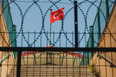 Turkey flag behind a fence and barbed wire. Turkey flag behind a fence and barbed wire against the blue sky royalty free stock photo