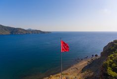 Turkey flag blowing in the wind. Drone photo of a bay in the mediterranean sea royalty free stock images