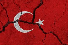 Turkey flag on the cracked earth. National flag of Turkey. Earthquake or drought concept stock photography