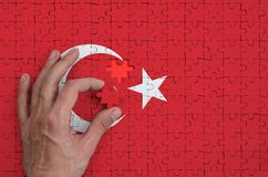 Turkey flag is depicted on a puzzle, which the man`s hand completes to fold.  vector illustration