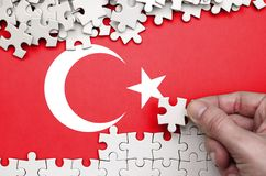 Turkey flag is depicted on a table on which the human hand folds a puzzle of white color.  royalty free stock photography