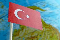 Turkey flag with a globe map as a background. Macro royalty free stock image
