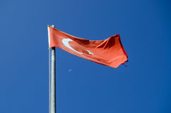 Turkey Flag and Moon. View of the red flag of Turkey with a crescent moon and in the far distance, a crescent moon Stock Image