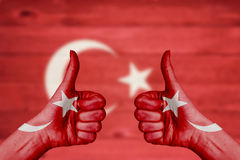 Turkey flag painted on female hands thumbs up. With blurry wooden background royalty free stock image