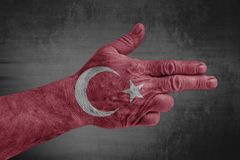 Turkey flag painted on male hand like a gun. Isolated stock photo