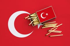 Turkey flag is shown on an open matchbox, from which several matches fall and lies on a large flag.  stock images