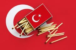 Turkey flag is shown on an open matchbox, from which several matches fall and lies on a large flag.  stock photography