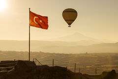 Turkey flag at sunrise with balloon and mountain in background. Royalty Free Stock Photos