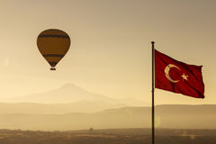 Turkey flag at sunrise with balloon and mountain Erciyes in back Royalty Free Stock Image