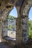Turkey, the ghost town of Kayakay, view of the city through the arch of a  church. Turkey, the ghost town of Kayakay, view of the city through the arch of a Royalty Free Stock Images